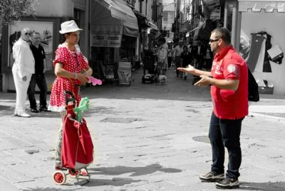 People dressed in red customes talking in Spanish